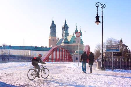 Poznan Cathedral and The Bishop Jordan Bridge over Warta River in the winter sunny day, Poznan, Poland 写真素材