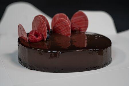 Round glazed chocolate cake with berries on top
