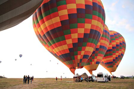 Preparing for take-off hot air balloons with tourists on sunrise