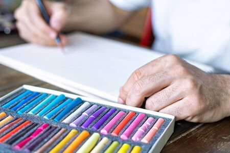 artist painting with a pastel crayon chalk on a white sheet of paper and box with pastel chalks in different colour