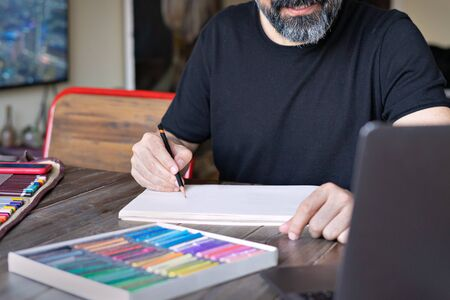 person learning e painting with pencil and pastel crayon chalk on sketchbook in front of laptop with palette of pastel chalks on the wooden table.