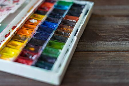 Set of watercolor paints and paintbrushes for painting closeup. Selective focus. wooden background. Copy space