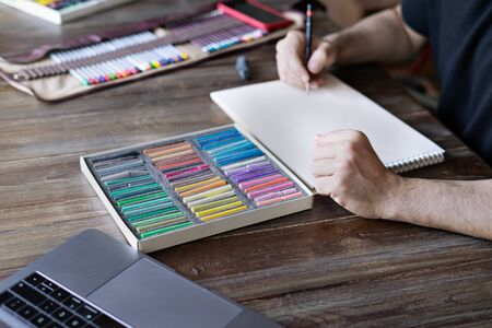 man artist painting with pencil and pastel crayon chalks on paper in front of laptop. Learning painting online education