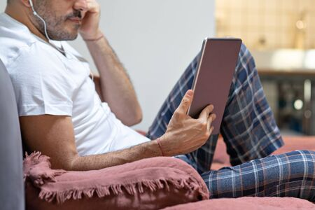man holding using digital tablet and headphones in bed at home with pijama. Online education, working, video call Foto de archivo