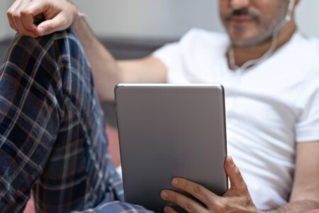 man holding using digital tablet and headphones in bed at home with pijama. Online education, working, video call