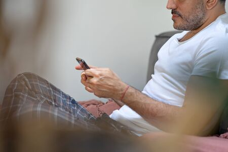man holding usings smartphone and talking by phone in bed, relaxing at home with casual pijama, searching in internet Foto de archivo