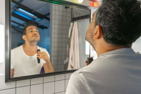 handsome bearded man is shaving his face and neck with trimmer machine in front of bathroom mirror Zdjęcie Seryjne