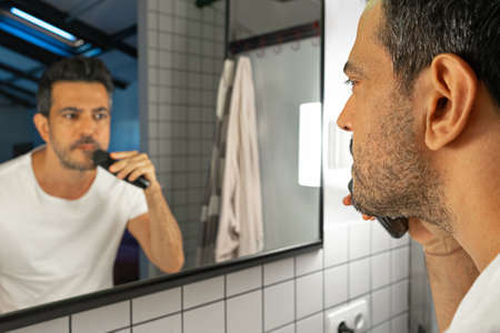 handsome man is shaving his beard with trimmer machine in front of bathroom mirror Zdjęcie Seryjne