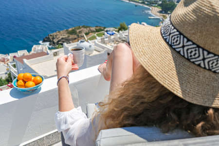 Beautiful young woman straw hat and coffee cup sitting on white terrace balcony of house or hotel with Sea View