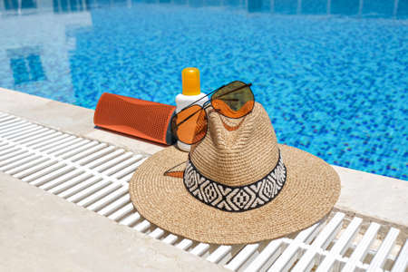 orange coloured beach accessories near swimming pool. Sun cream, sunglasses, music speaker and straw hat