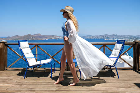 Beautiful young woman in white dress and bikini straw hat on white terrace balcony of house or hotel with Sea View