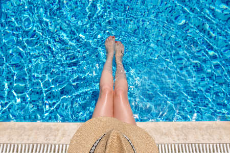 Young woman in straw hat sunbathing sitting on the edge of swimming pool with legs in water. top view