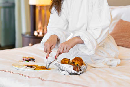 woman eating breakfast in the bed in hotel. Fresh croissant bread fruits in plate.