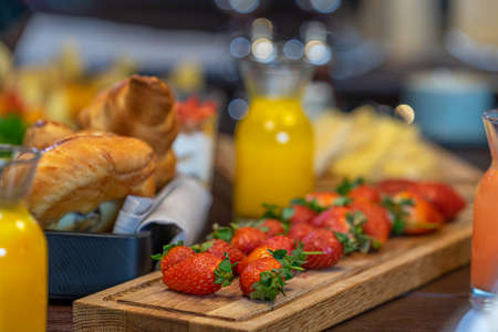 Breakfast buffet served with, orange juice, croissants and strawberry