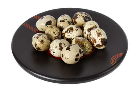 quail eggs on a black plate  isolated on white