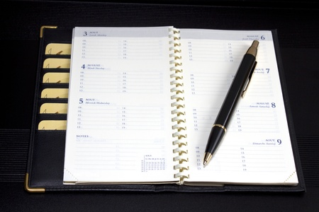 notepad with  spiral and pen on black background