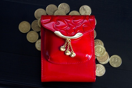 Red glossy leather purse with gold metal  and  gold coins on black background