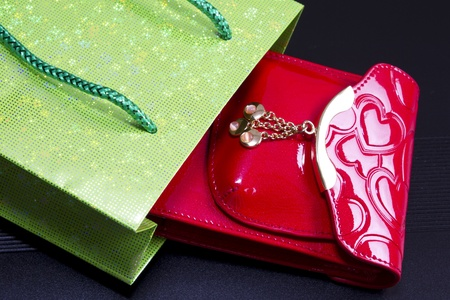 Red glossy leather purse with gold metal  and  green bag   on black Stock Photo