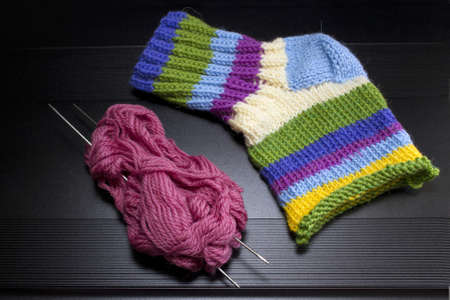 Pink threads, spokes and  multi-colored knitted socks Stock Photo