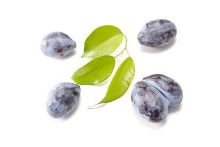 Some plums with green leaves isolated on white