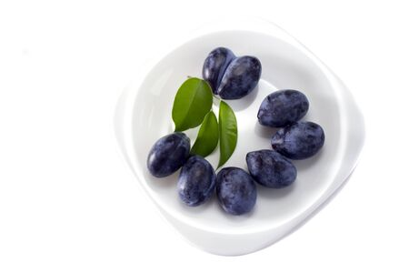Some plums with green leaves on the plate