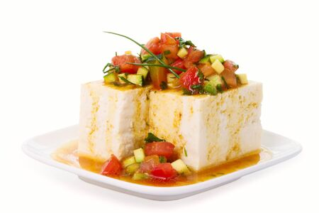 Tofu topped with soy sauce, olive oil and vegetables. Stock Photo