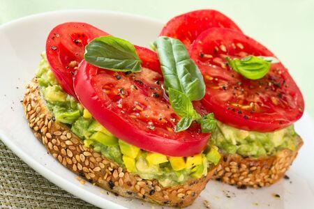 Avocado mash,  tomato and basil on slice of toasted bread.
