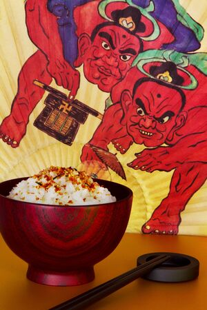 Rice bowl and chopsticks with Japanese fan in the background.