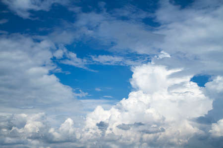 Background of blue sky with white cumulus clouds.