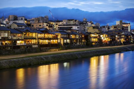 Night view on the Kamogawa river embankment in Kyoto. Restaurant lights reflected in the river.