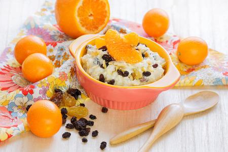 Oatmeal porridge with raisins and tangerines. Banco de Imagens