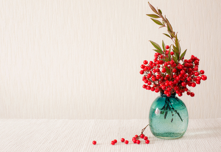 Japanese vase with red berries of Sacred Bamboo Nandina Domestica. Place for text