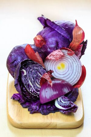 Red cabbage and onions on a cutting board.