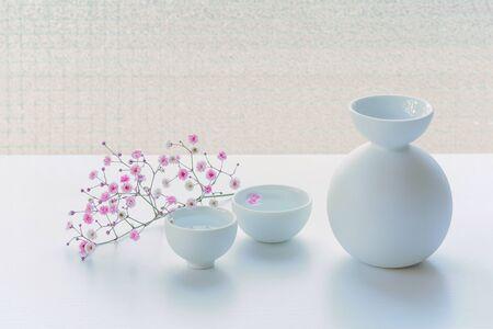 Butelka w stylu japońskim na białym stole, ozdobiona różowymi drobnymi kwiatuszkami.