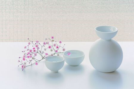 Bottle of Japanese style on a white table, decorated with pink small flowers.