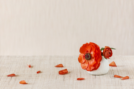 Anemone flower in a small Japanese vase on the table. Blurred background. Place for text.