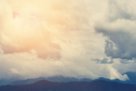 Mountain landscape with peaks covered by picturesque clouds.  Background of mountain and cloudy sky. Toned.