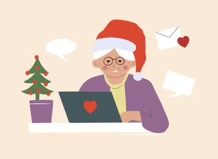 An elderly grandmother in a Santa Claus hat writes Christmas greeting messages online. Communication over the Internet at a distance.
