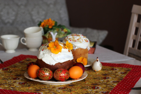 breakfast or brunch table setting for easter meal with friends and family around the table served with bright tablecloth with traditional home made cake, colored eggs, decorations, flowers. Stock Photo