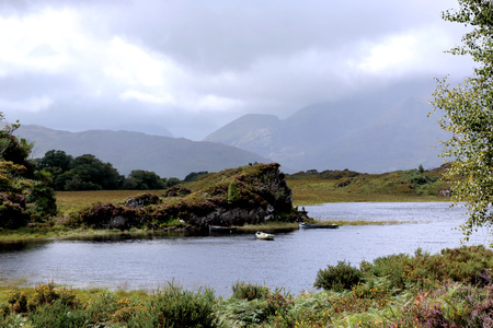 Irish scenery landscape. Lake and mountain. Cloudy day. A lot of plants. Some boats. Calm  mood.