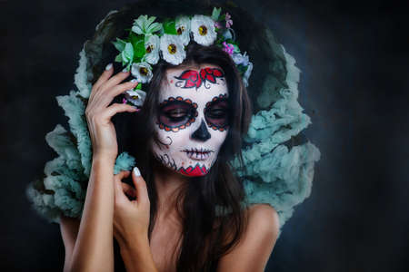 Portrait of a young woman with make-up sugar skull with flowers in her hair on a dark background looks down. Dia de los muertos. Day of The Dead. Halloween costume and make-up. Stock Photo