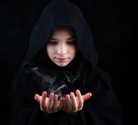 A girl in a witch's cloak with a magic wand in his hand conjures magic. Halloween outfit