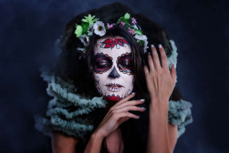 Young woman with sugar skull makeup. Dia de los muertos. Day of The Dead. Halloween costume and make-up. Portrait of Calavera Catrina