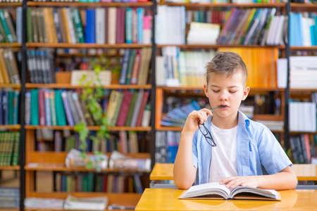 A boy in a blue shirt in a library reads a book, thoughtfully nibbles a shackle of glasses while looking into a book Standard-Bild