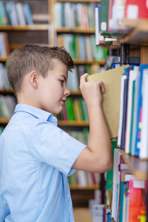 A boy in a blue shirt in a library takes a book from a bookshelf
