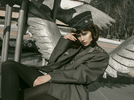 girl in uniform against the background of military equipment 版權商用圖片