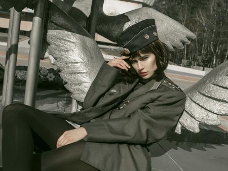girl in uniform against the background of military equipment Standard-Bild