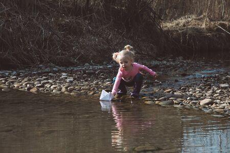 Little girl launches paper boats Archivio Fotografico