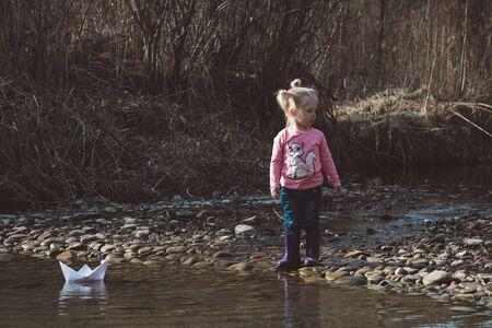 Little girl launches paper boats
