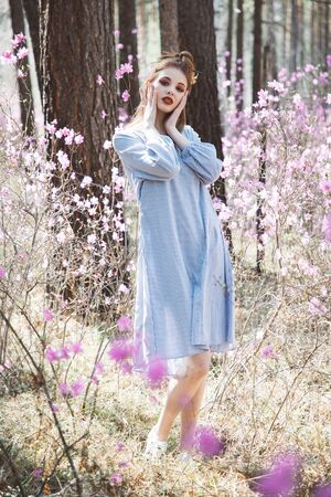 A girl dressed in Japanese style in a flowering forest among pink flowers Stok Fotoğraf